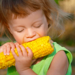 Girl-Taking-a-Bite-of-Corn-1024x600.png